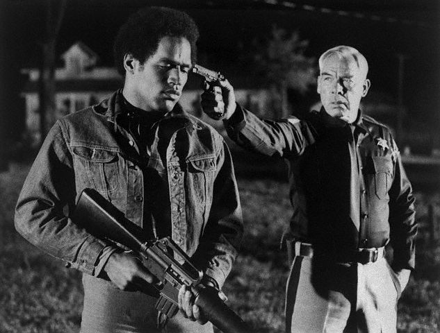 What a way to start a movie career - in trouble with Lee Marvin! Playing a sheriff, Marvin holds a gun to the head of O.J. Simpson to prevent a violent clash between black militants and the Klu Klux Klan in a scene from the Paramount release . Football's O.J. is making his film debut in the movie.