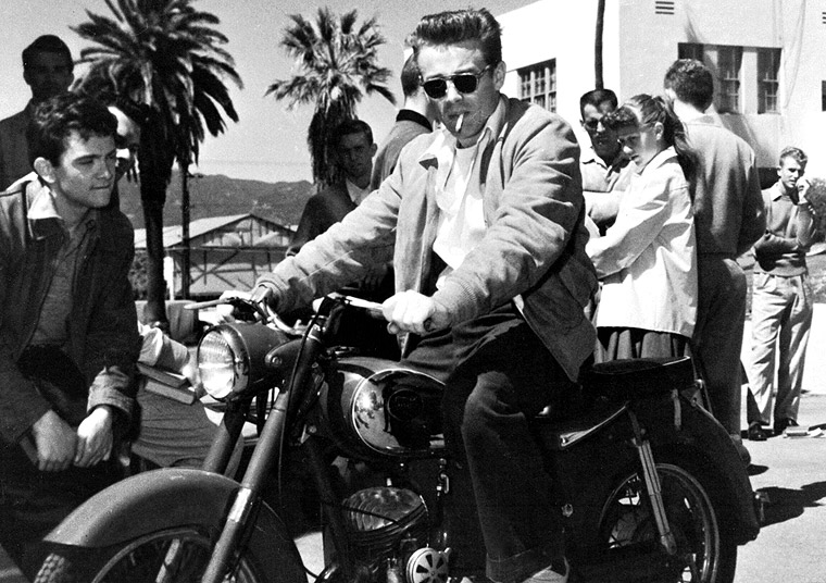 """James Dean on the set of """"Rebel Without a Cause"""" astride his Triumph T5 Trophy."""