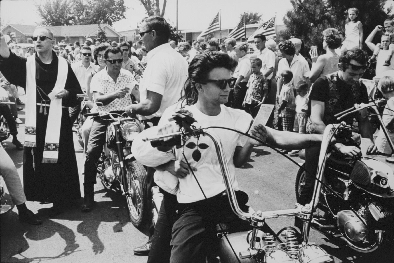"""""""Seventeenth Annual World's Largest Motorcycle Blessing, St. Christopher Shrine, Midlothian, Illinois"""" from The Bikeriders by Danny Lyon."""