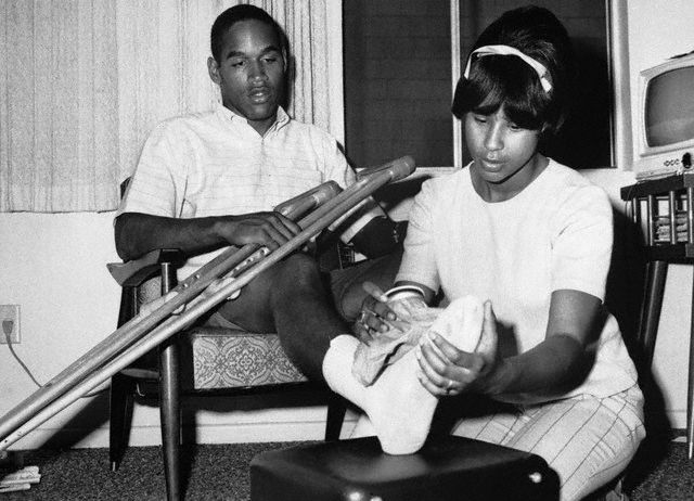O.J. Simpson, the nation's leading ground gainer from USC gets an ice application on his bandaged right foot from his wife Marquerite, ca. 1967.