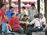 Seniors playing chess outside Chinatown's Buddha Tooth Relic Temple.