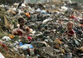 Children of rag-pickers stand amid a heap of garbage on the outskirts of New Delhi in 2006.