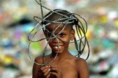 A boy looks on as he collects recyclable materials at a garbage dump in New Delhi in 2006.