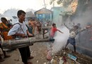 Children play in the fumes of a municipality fumigant sprayer in a slum area in the northeastern Indian city of Siliguri, Oct. 5, 2006.