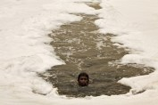 A boy swims in the polluted water of the Yamuna River to dive for offerings thrown in by worshippers amid a dust haze in New Delhi during World Environment Day in 2010.