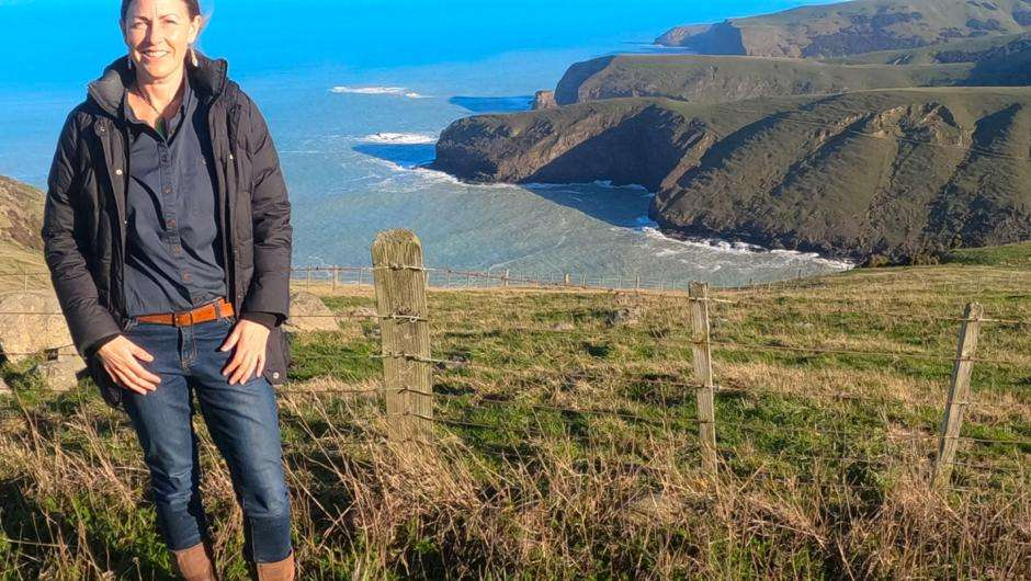 Woman standing at the top of sea cliffs Banks Peninsula