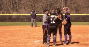 Students huddle during softball