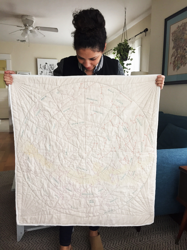 A picture of the author holding up a cream quilt with constellations quilted on it.
