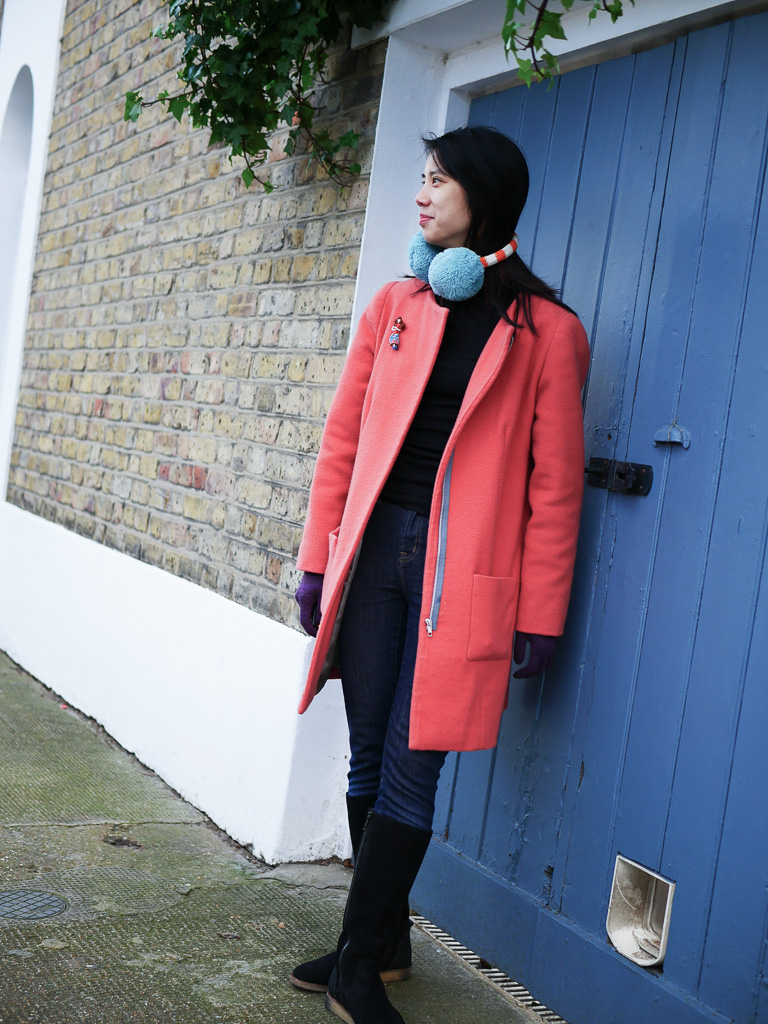 Kate wears a bright coral coat with a blue zipper, and matching bright blue earmuffs. She stands in front of a blue door punctuating a brick wall.