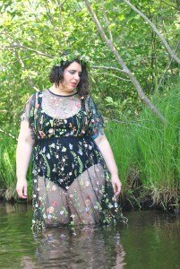 Shannon standing in knee-length water in front of greenery, wearing a sheer dress embroidered with flowers over a black bodysuit. Shannon wears a flower crown, sparkly blue eyeshadow, and looks down and to one side.
