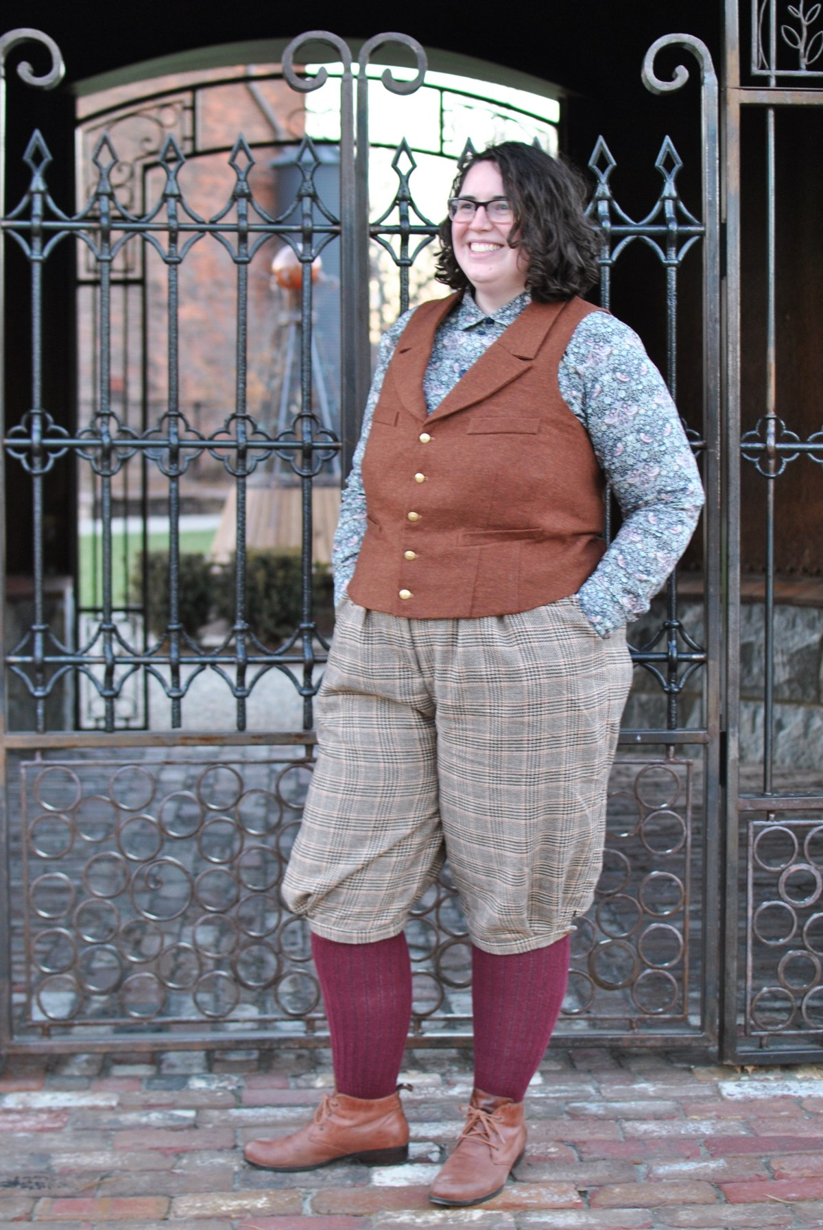 Shannon poses in front of a gate, wearing tan plaid knickerpockers, a rust vest, burgundy knee-socks, and a blue floral button-down shirt