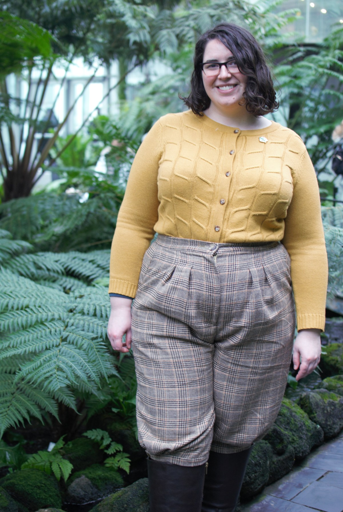 Shannon poses in front of a garden, wearing the plaid knickerbockers and a butter-yellow cardigan. The shot shows details of the pleating on the front of the knickerbockers.