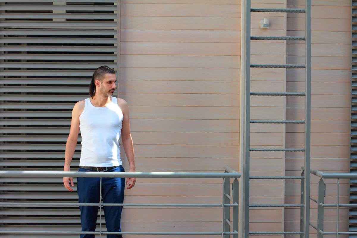 Joost wearing blue jeans and a white tank top or vest.