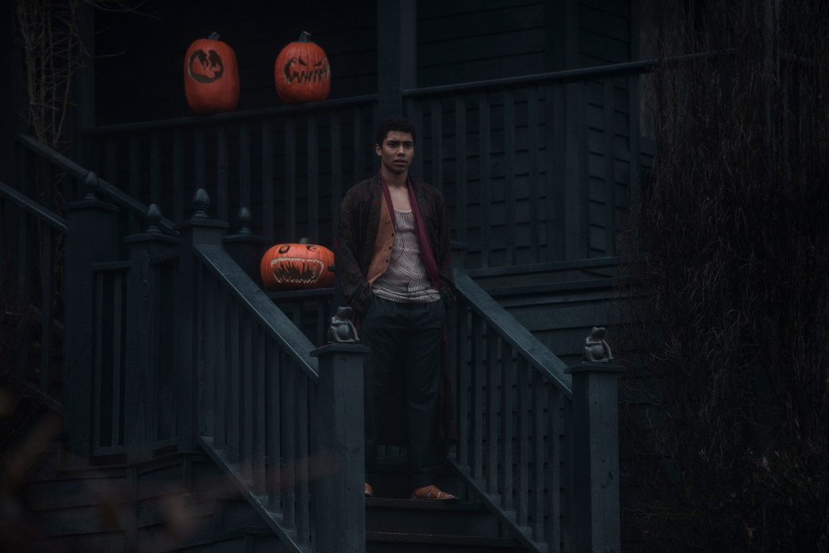 Ambrose Spellman stands on an outdoor staircase decorated with jack-o-lanterns. He wears a dark smoking jacket over a ratty undershirt and sweatpants.