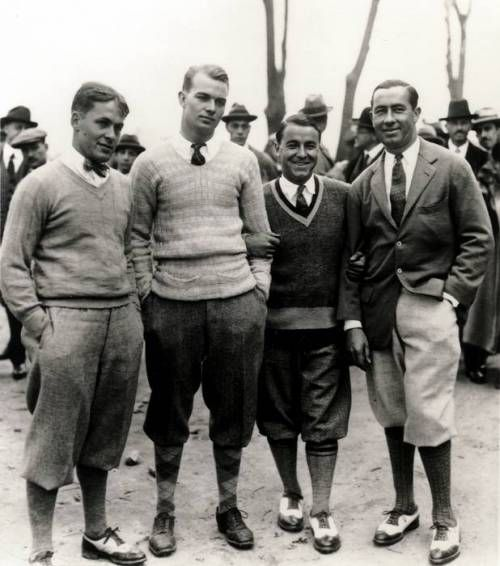 A black and white photo of four men standing close together and facing the camera. They all wear knickerbockers, loose pants that end below the knee with a cuff, shirts and ties, and either sweaters or blazers. They all stand casually, some with hands in pockets.