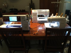 dining table set up with 3 machines: 1 serger, 1 sewing machine with top stitch thread, 1 sewing machine set up with seaming thread