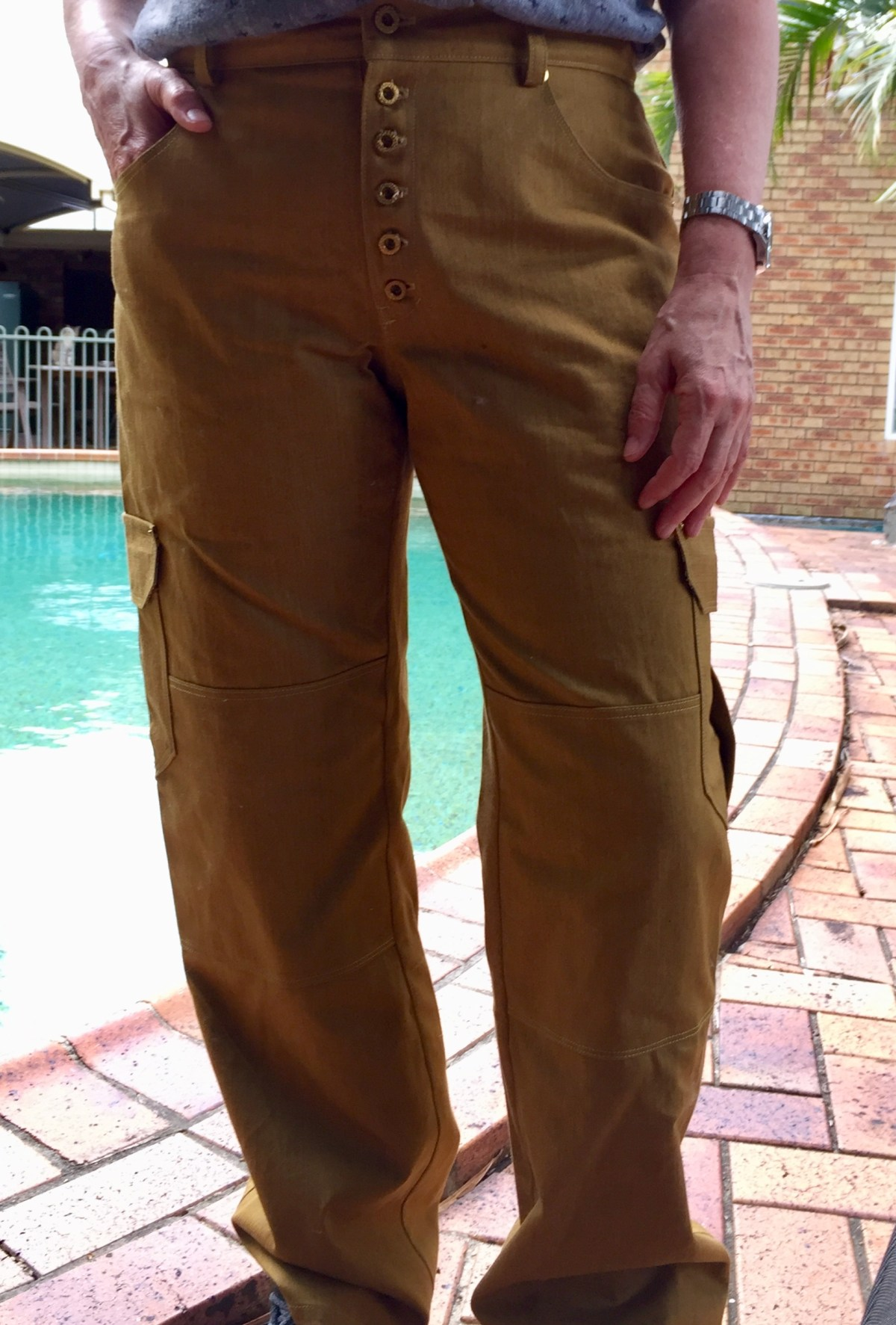 Front view of the author wearing the trousers, with brassy buttons down the fly