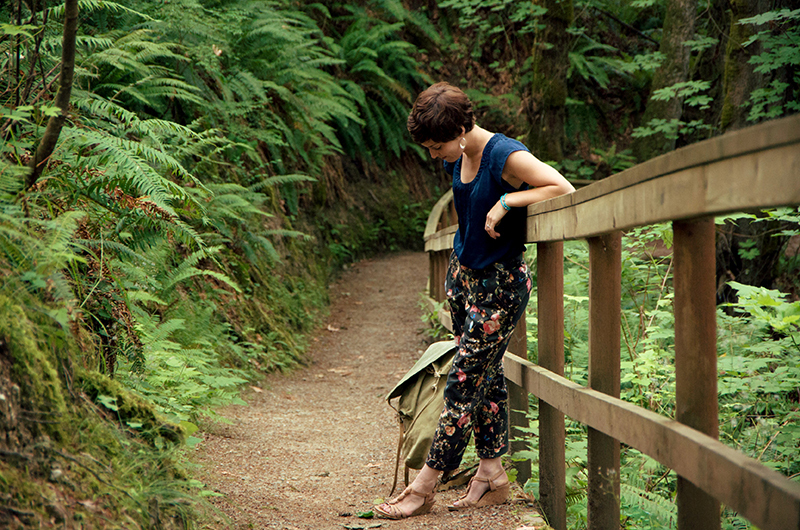 Morgan standing on a fern gully trail leaning against a wooden hand railing. She is wearing floral Jedediah trousers.