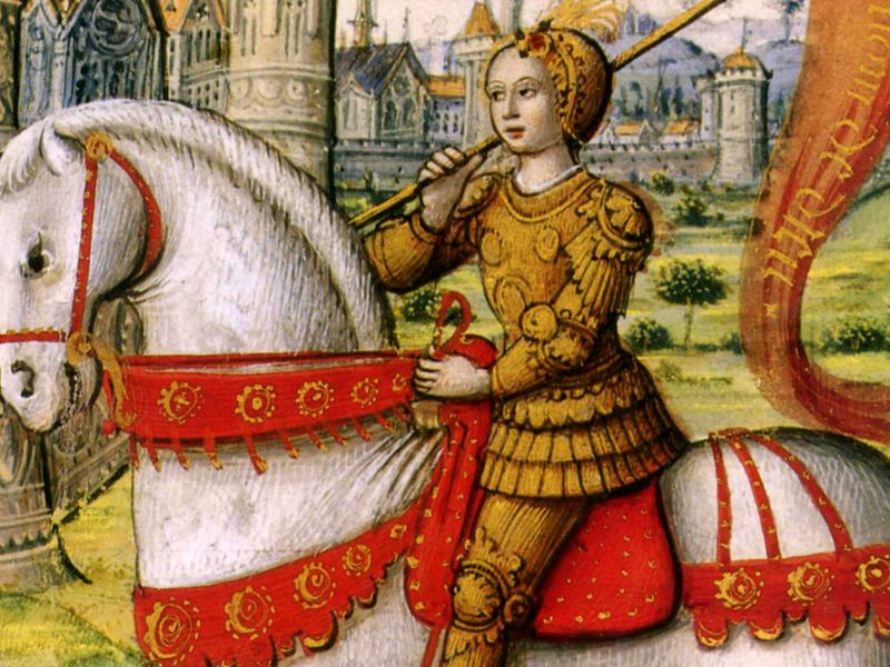 Image of Joan of Arc dressed in dark yellow tunic and pants, riding a horse with red livery.  French castle in the background.