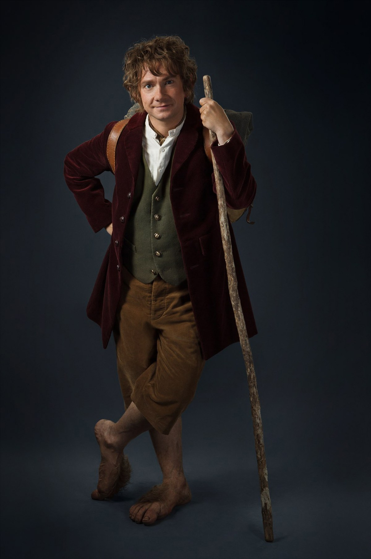 A promotional shot of actor Martin Freeman as Bilbo Baggins, wearing short brown trousers, a green vest, and a burgundy blazer. He leans on a walking stick with a hand on one hip.