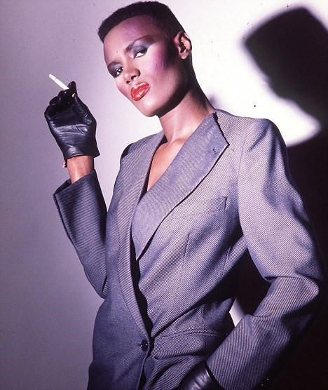Grace Jones, a black woman with a flat top and dramatic makeup, wears a gray suit with no upper collar and a twill weave. She holds a cigarette in one raised hand in a black leather glove.