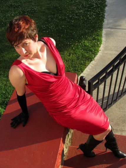 The author leaning back looking up into the camera, in a slinky red dress, black opera gloves, and black stiletto boots.