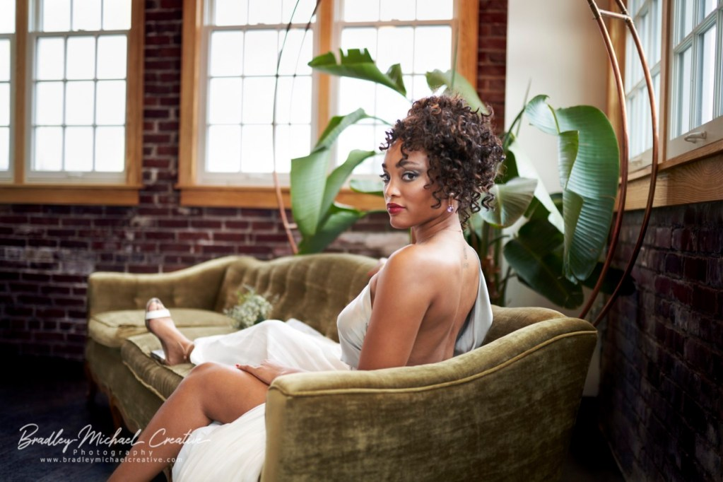 Professional photo of a model wearing one of Leila's garments. The model sits on an elegant couch, reclining gracefully, bathed in natural light and draped artfully in a backless gown, and she looks over her shoulder at the camera.