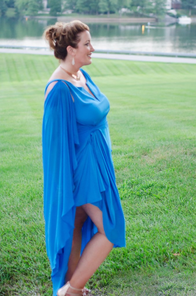A woman poses in a striking, drapey blue gown, with fluid sleeves and a revealing swoosh of fabric around her legs.