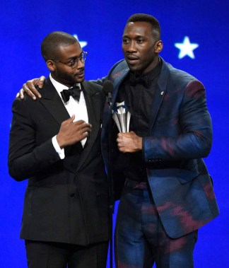 Mahershala Ali, a black man, holds a microphone while wearing a blue and fuschia suit over a dark shirt. He stands with his arm around the shoulders of another black man, who is wearing round glasses and a tuxedo.