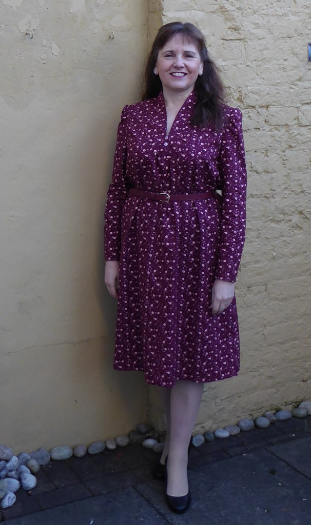 Elaine poses against a wall, wearing a red-violet floral button-down dress.