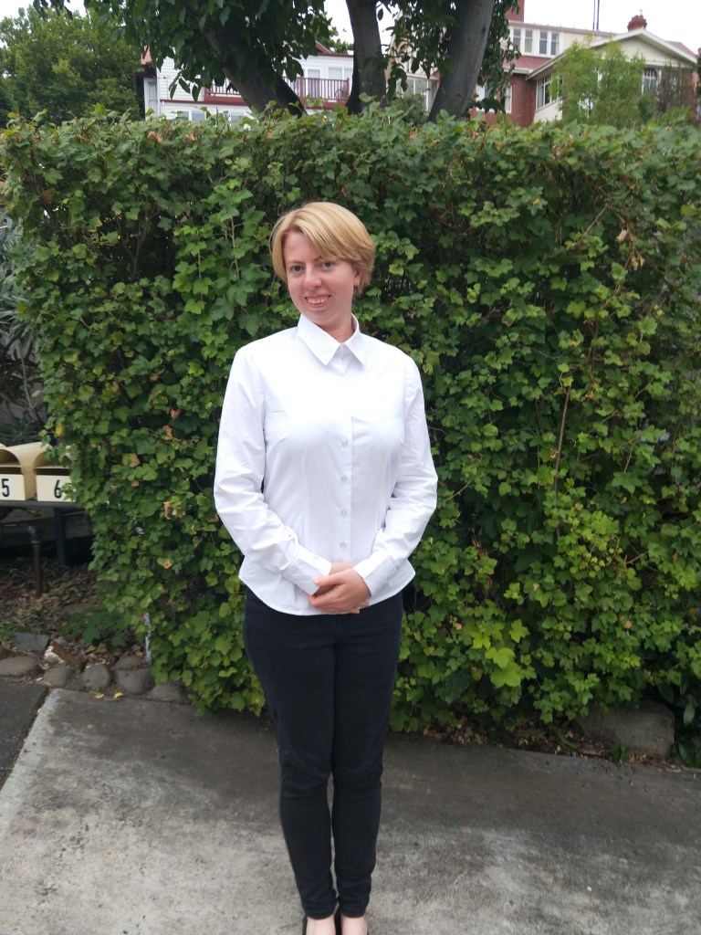 Tanita poses in a crisp white button-down shirt and dark trousers.