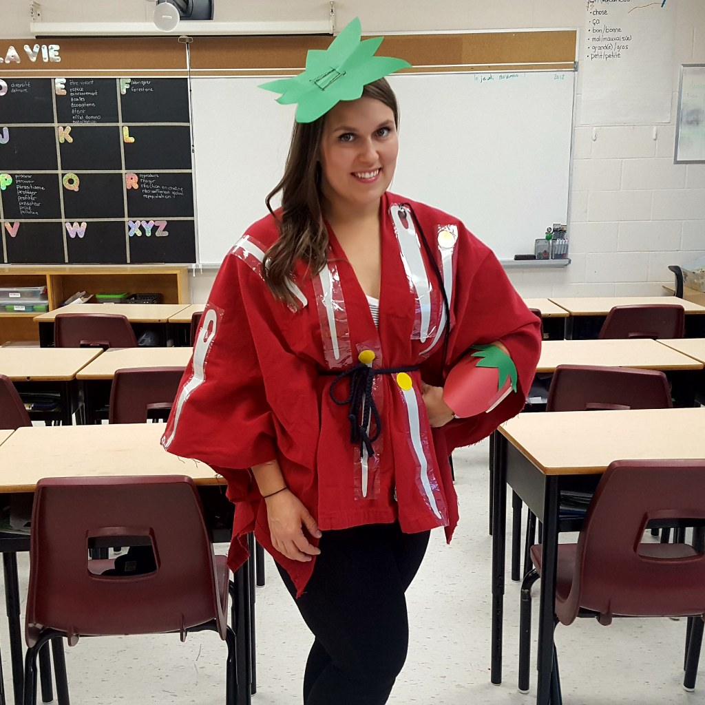 A picture of Sam in a classroom, dressed as a classic tomato pincushion!
