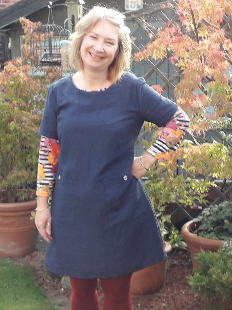 Mary stands in a garden, wearing a navy blue dress with contrasting stripes-and-floral sleeves and trim.