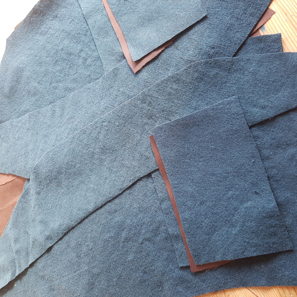 Teal wool fabric and brown lining fabric cut into the pieces to make the waistcoat.