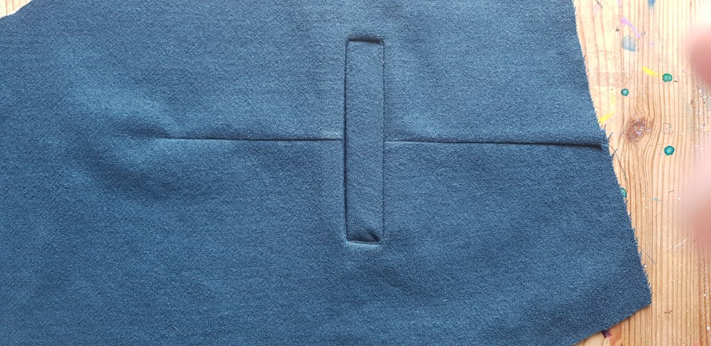A finished welt pocket in teal wool fabric.