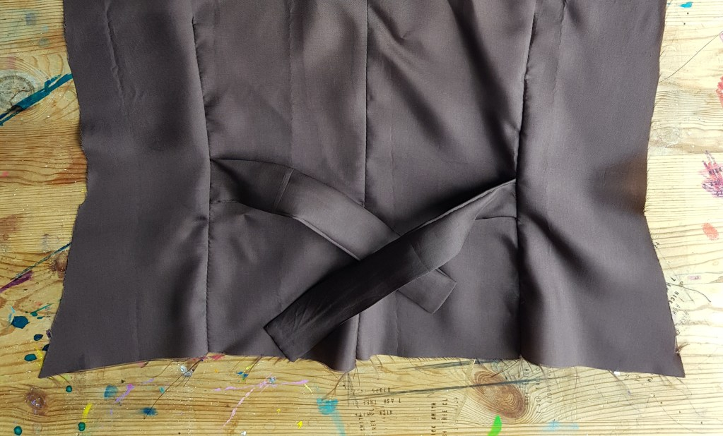 The back panel of the waistcoat, featuring a cinching belt in brown fabric.