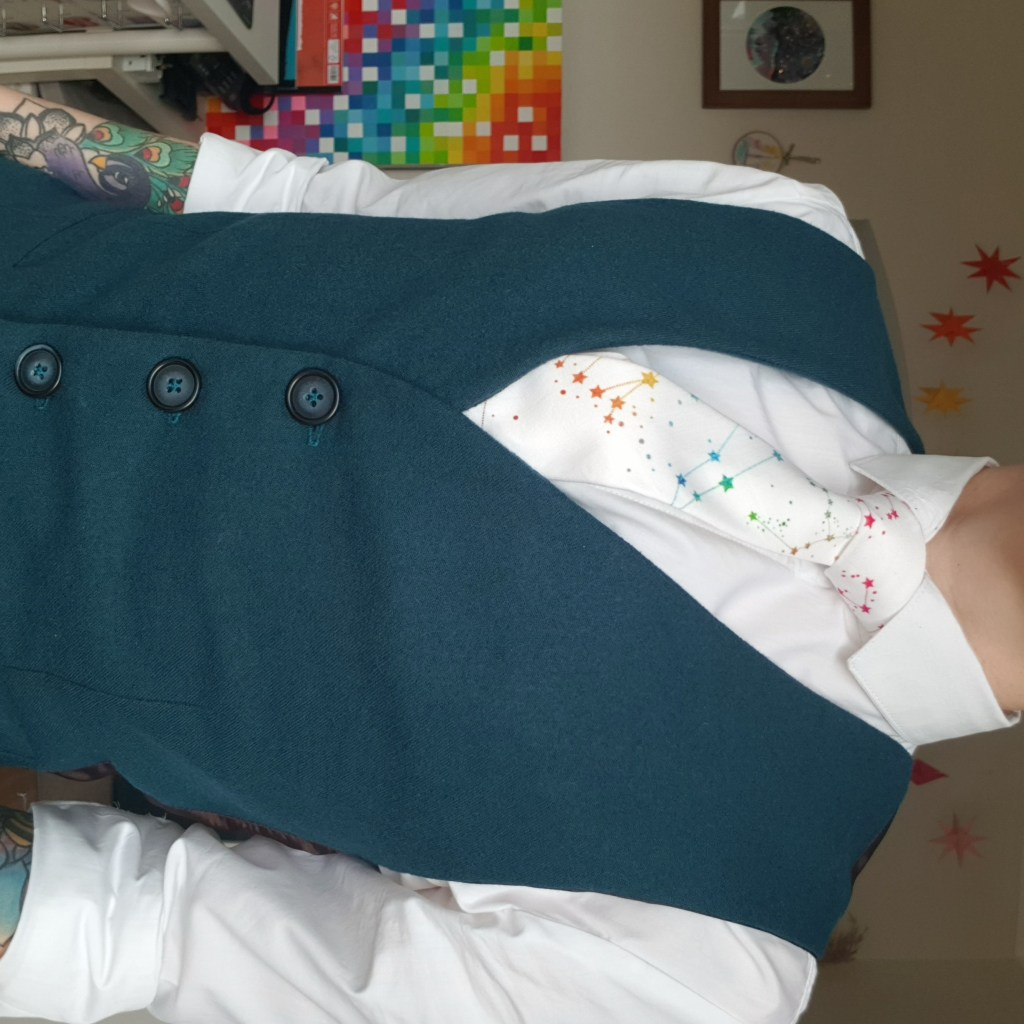 A cropped photo of the author, wearing the finished teal wool waistcoat, with a white shirt and a a white tie with rainbow constellations.