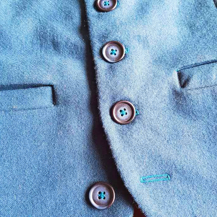 A close up of the buttonholes and buttons in the waistcoat.