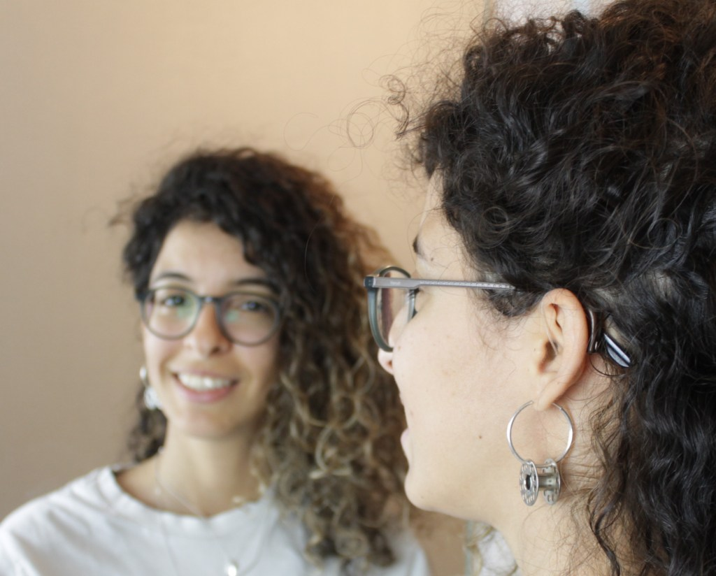 A curly hair woman with glasses standing in front of the mirror showing her left hearing device.