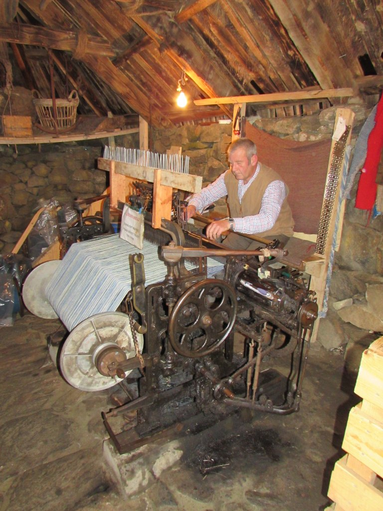 A weaver at work on a traditional loom in a wooden shed