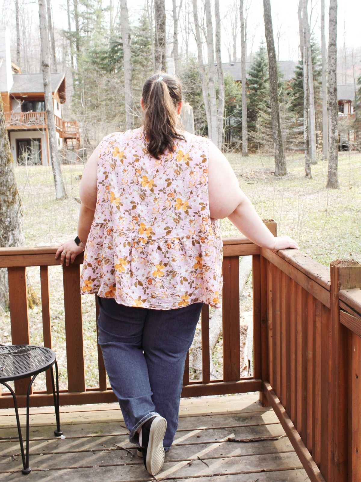 A woman stands against a deck railing facing away from the camera. Her brown hair is pulled back into a ponytail and she has bent her left knee casually. She is plus-sized and is wearing blue jeans and a sleeveless pink and yellow floral top with a gathered lower bodice. She looks off toward the woods and houses beyond the deck.