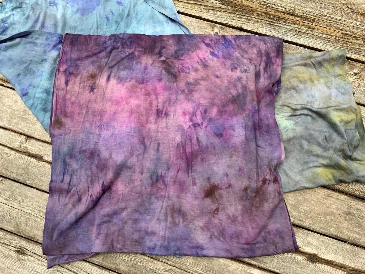 A cut of hand-dyed merino and silk jersey in shades of purple rests on top of two smaller cuts of the same fabric, one in blue with dark blue and purple details and one in gray with yellow details.