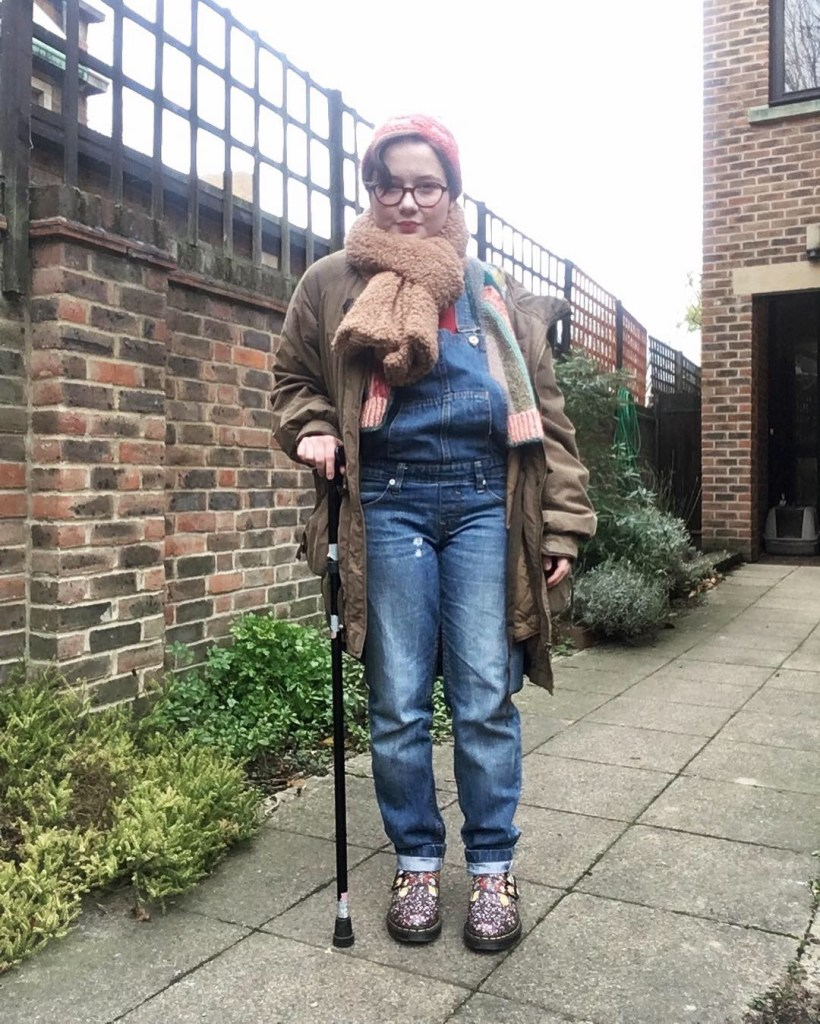 Photo of Anna outside in winter layers, using a walking cane.