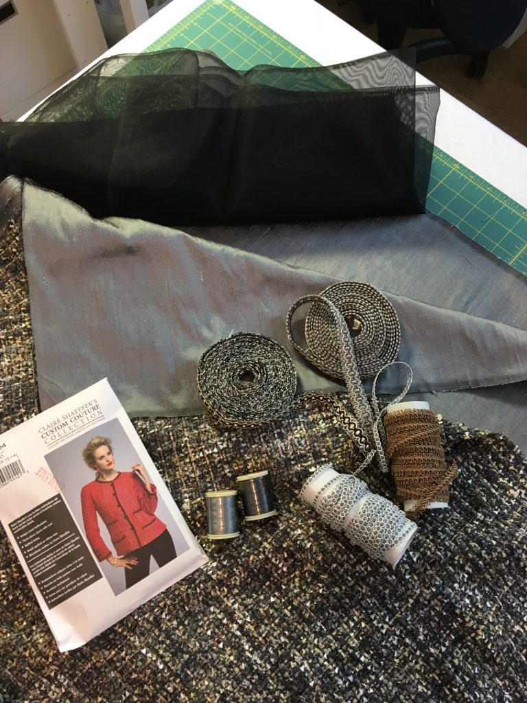 A mood board of some grey tweed fabric with rolls of trimmings, thread and a sewing pattern for a Chanel-style jacket.