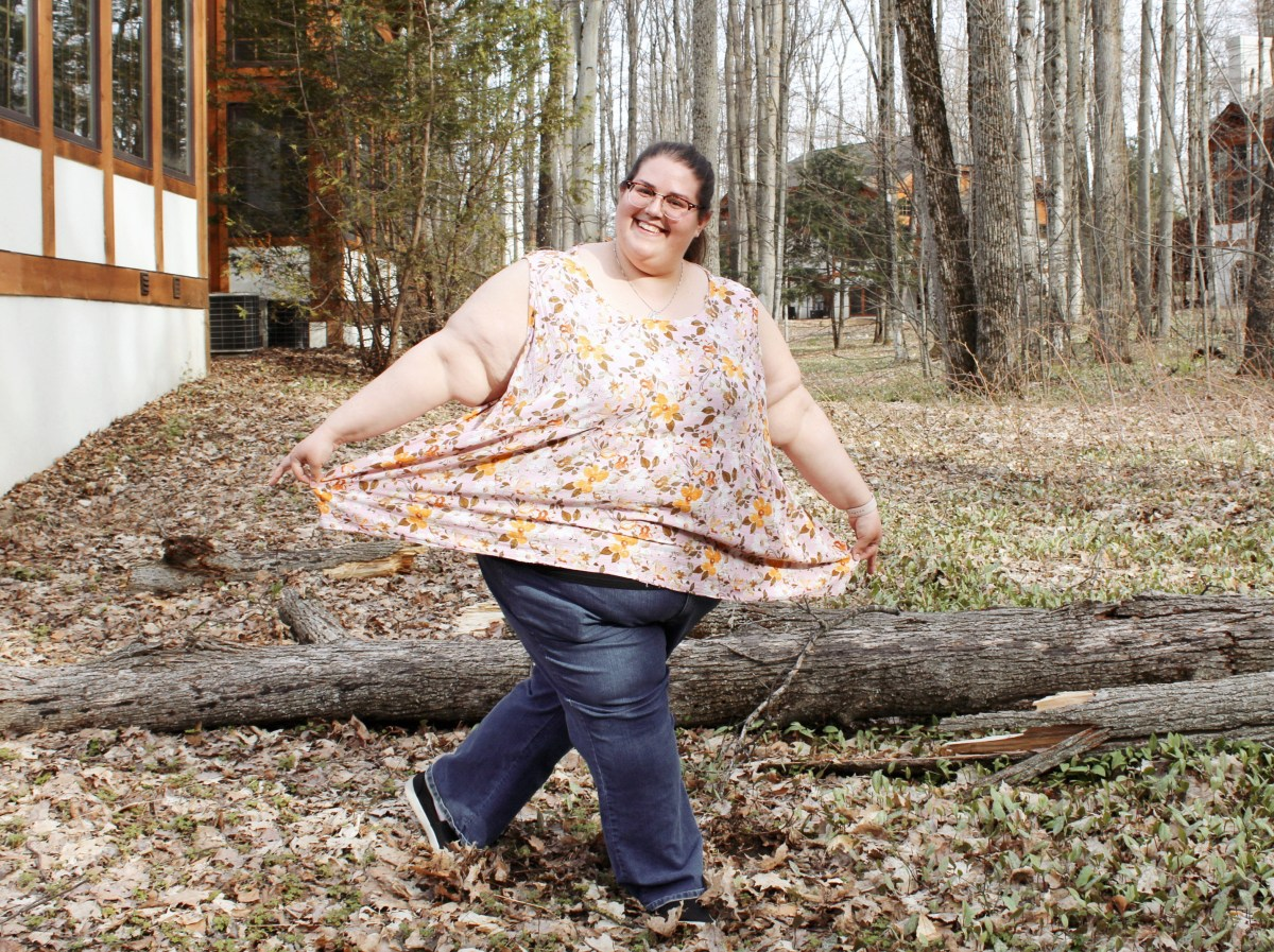 Jenn faces the camera and holds the sides of her blouse out away from her as far as they will go. She is smiling widely and poses as though she is about to curtsy. Woods, houses, fallen tree limbs, and fallen leaves are all around her. Jenn's blouse is a pink and yellow floral sleeveless top, which she wears with blue jeans and black sneakers.