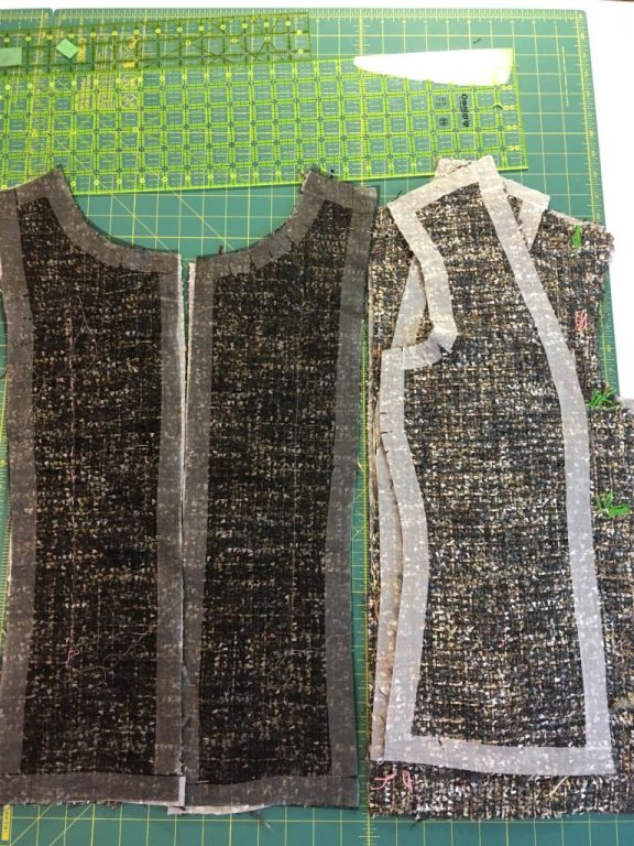 Several grey tweed bodice pieces on a cutting board. The bodice pieces have strips of interfacing around the seam allowances.
