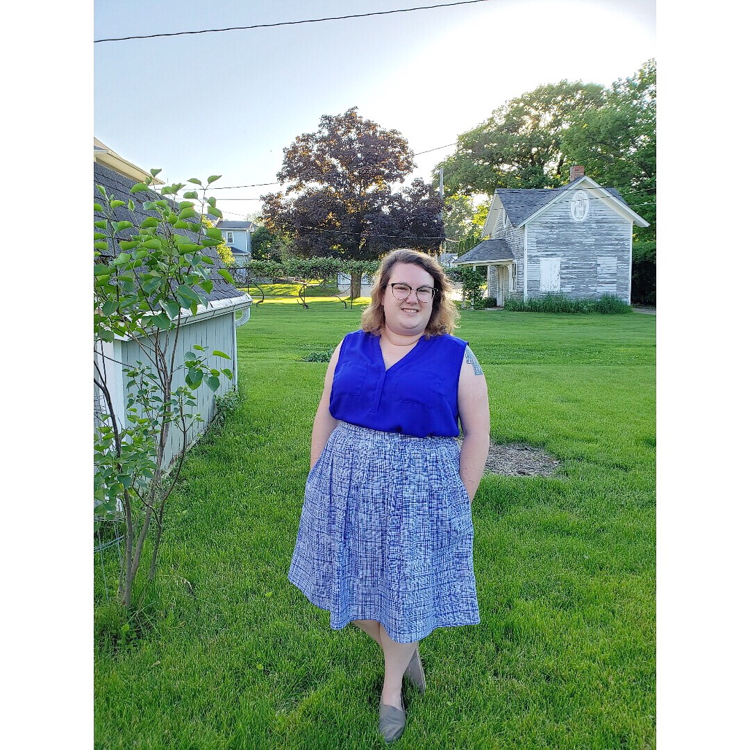 Erin's photo shows her standing in a farm field, wearing a blue and white skirt (with pockets!) and a blue blouse.
