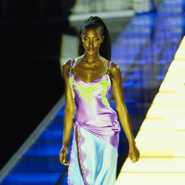 A tall black woman with hair in a high ponytail walks along a catwalk wearing an elaborate slip dress in shades of lilac, aqua and lime green.