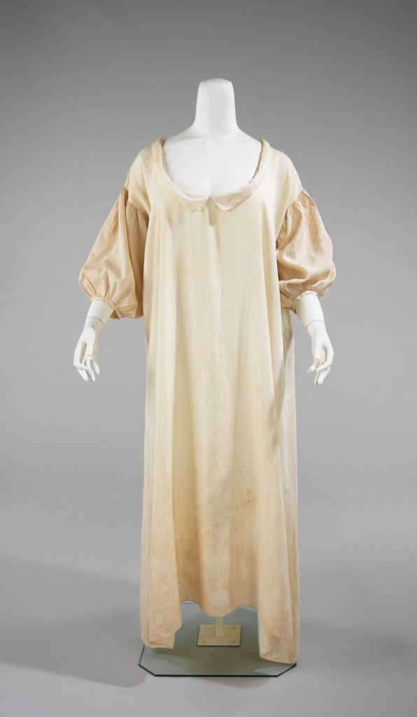 A mannequin wearing a scoop neck, full length nightgown with a peter pan collar and full, gathered three-quarter sleeves