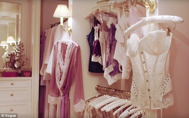 A walk in closet displaying rows of satin and lace slips and robes. In the foreground hangs a white lace corset.